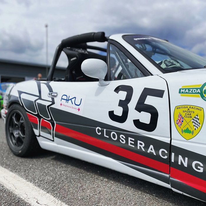 A closer racing Mazda MX5 with race livery including the AKU Society logo