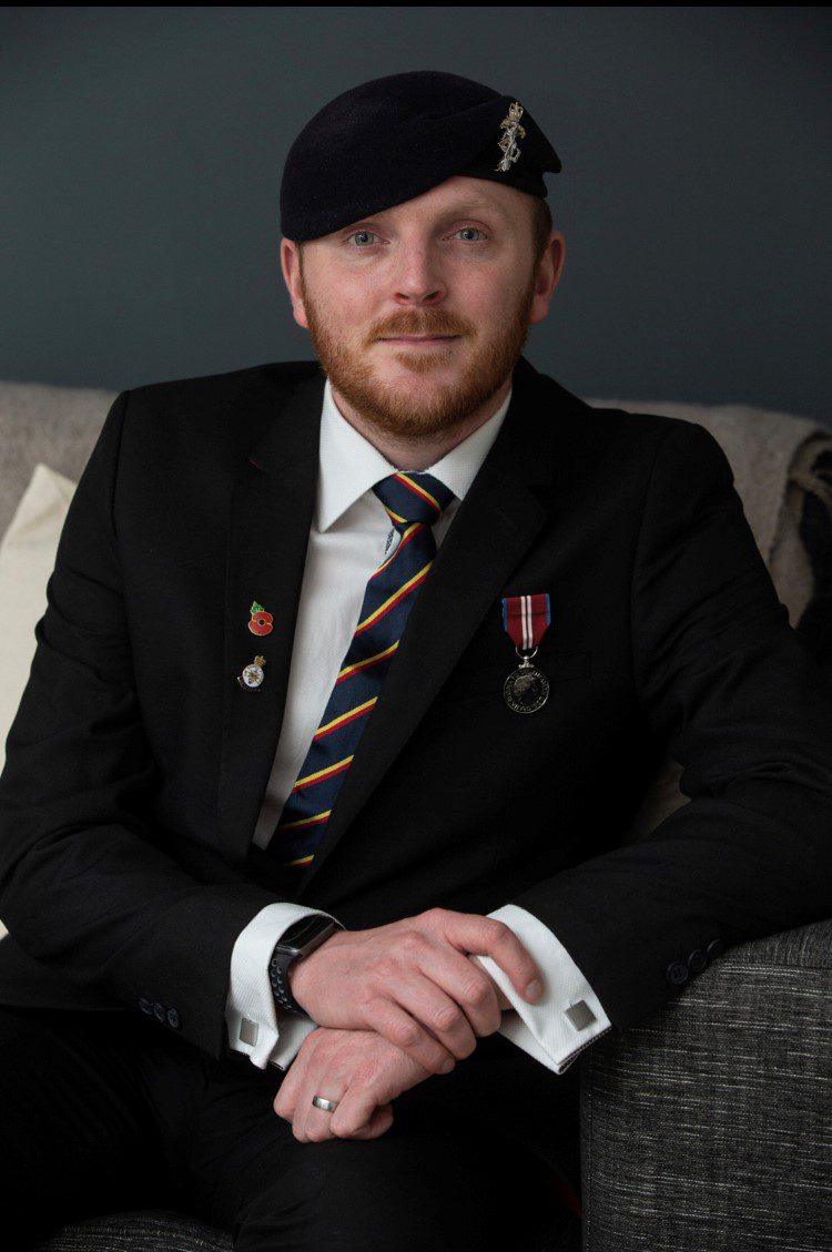 Mike Poses for a photo in a suit with a beret and cap badge of the Royal Electrical and Mechanical Engineers and regimental tie. He has a medal on pinned to his blazer.